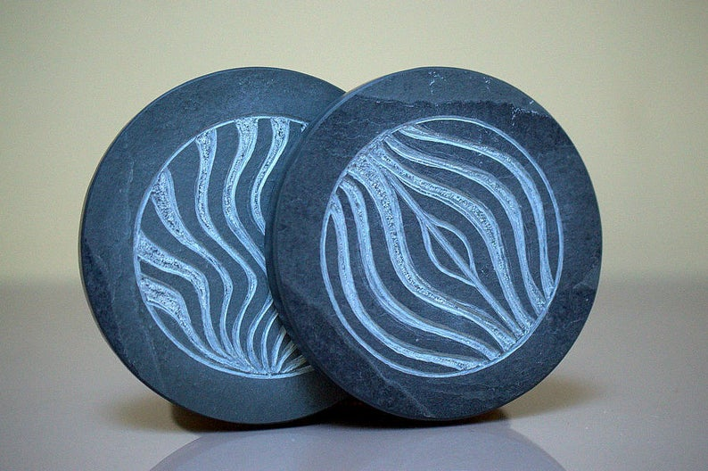 Two round shape abstract carved stone coasters