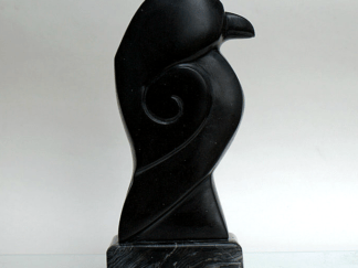Black stone raven carving from side view.